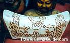 A jade pillow with the picture of twin dragons playing with a pearl
