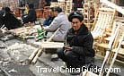 People selling various kinds of woodwork at Kaili market, Guizhou.