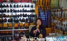 The shop owner is performing traditional Chinese music with the musical instrument Hulusi.