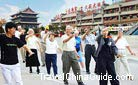 A Chinese coach is teaching foreigners to play Tai Chi Quan.