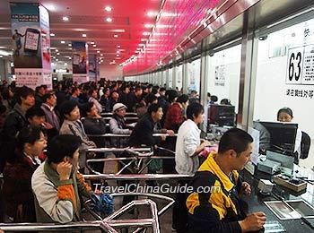 Passengers Queue to Buy Train Tickets