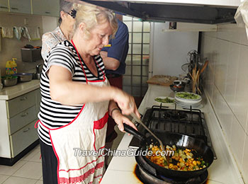 Our client learning to cook Chinese dishes at a local family